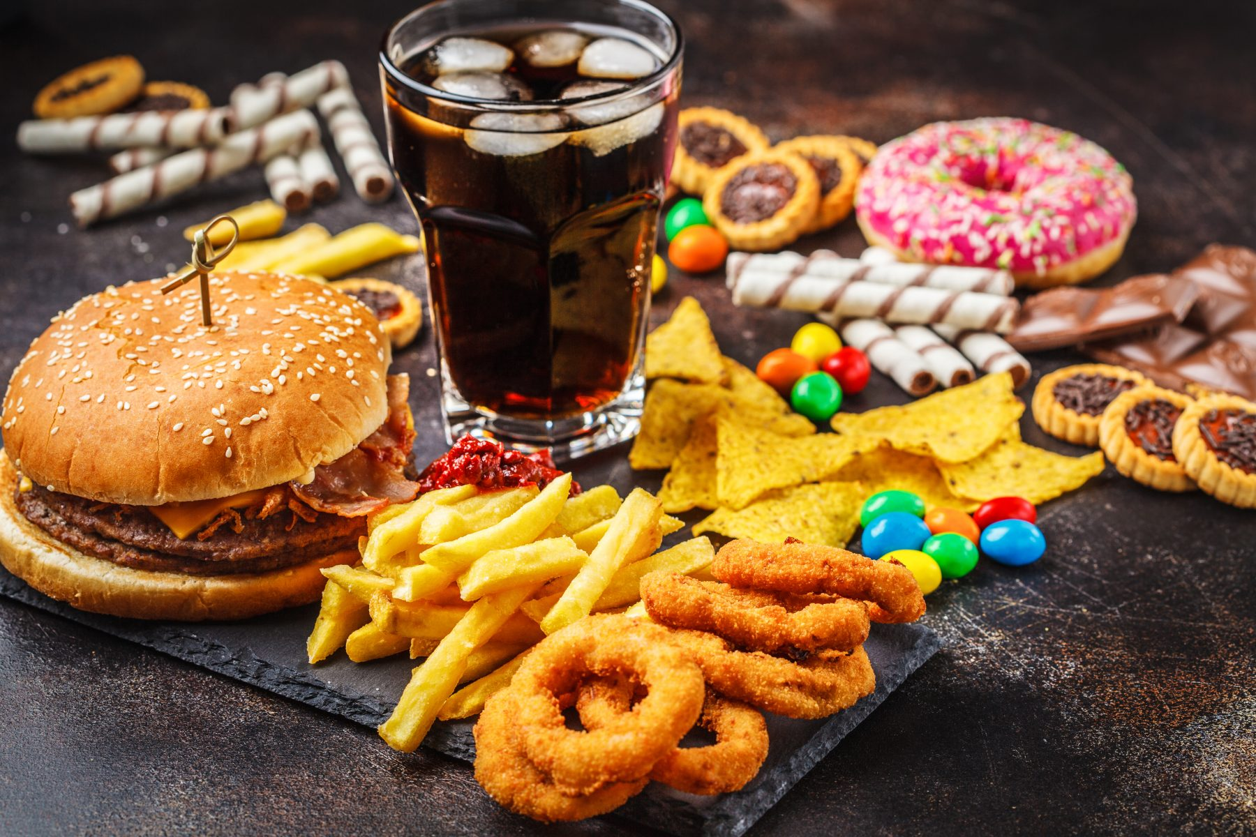 Burger, sweets, chips, chocolate, donuts, soda served on a dark background table